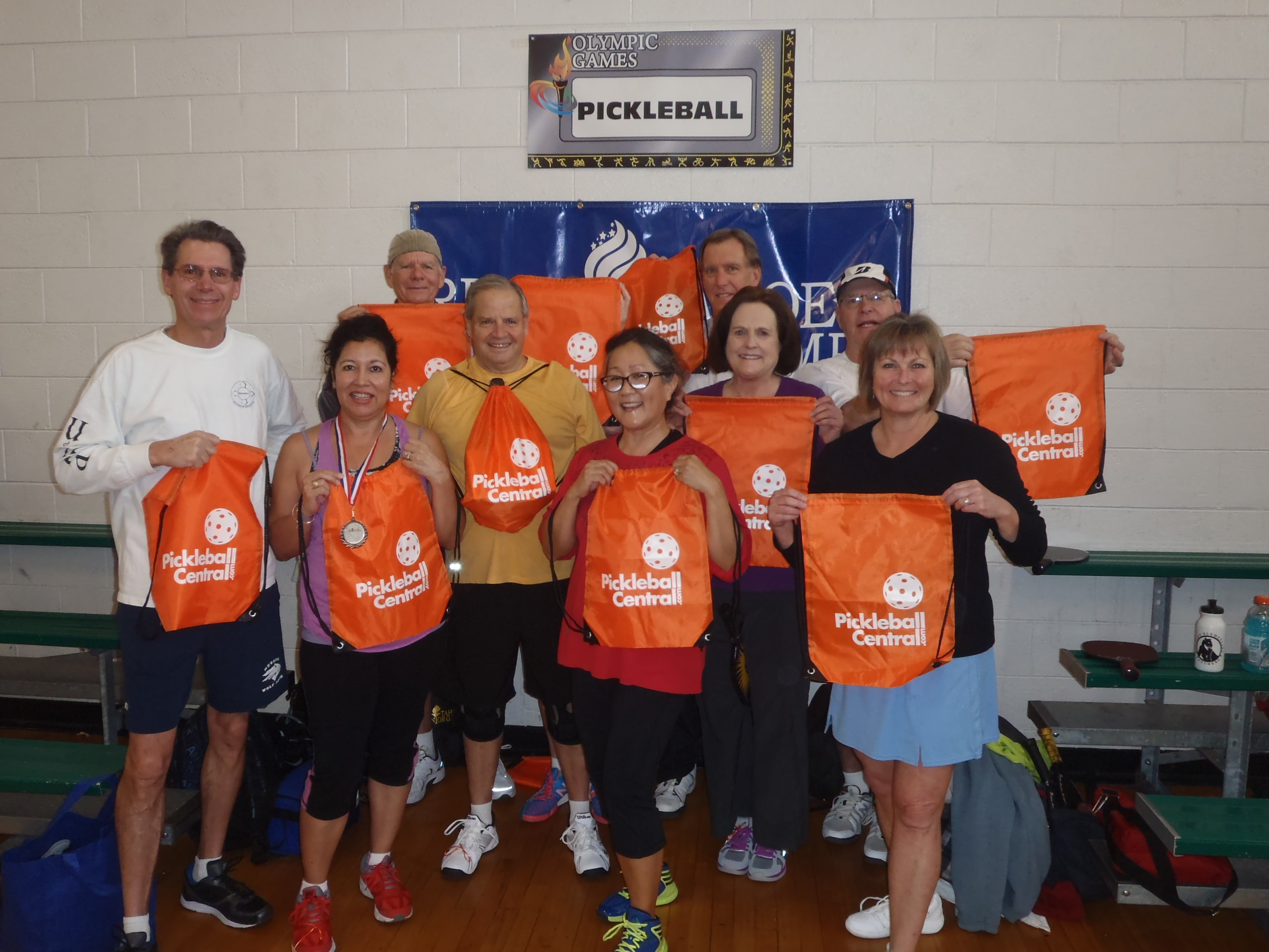 Pickleball players at a tournament holding goodie bags from PickleballCentral.com